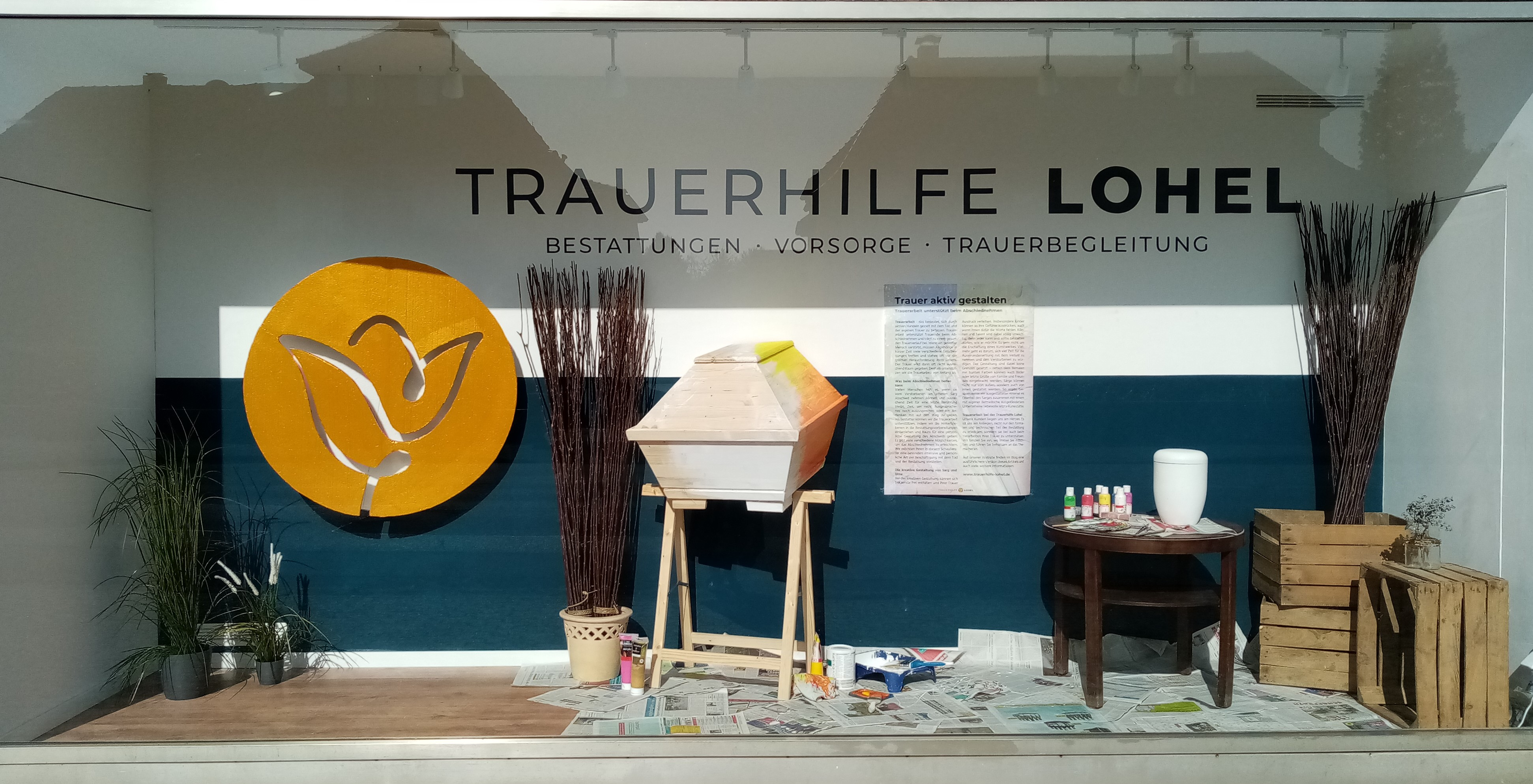 Das Schaufenster der Trauerhilfe Lohel in Xanten zum Thema Trauerarbeit. Ausgestellt sind Sarg und Urne zur freien Gestaltung mit Malutensilien.