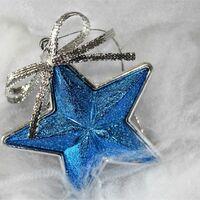 Ein glänzender blauer Weihnachststern mit silberner Schleife.