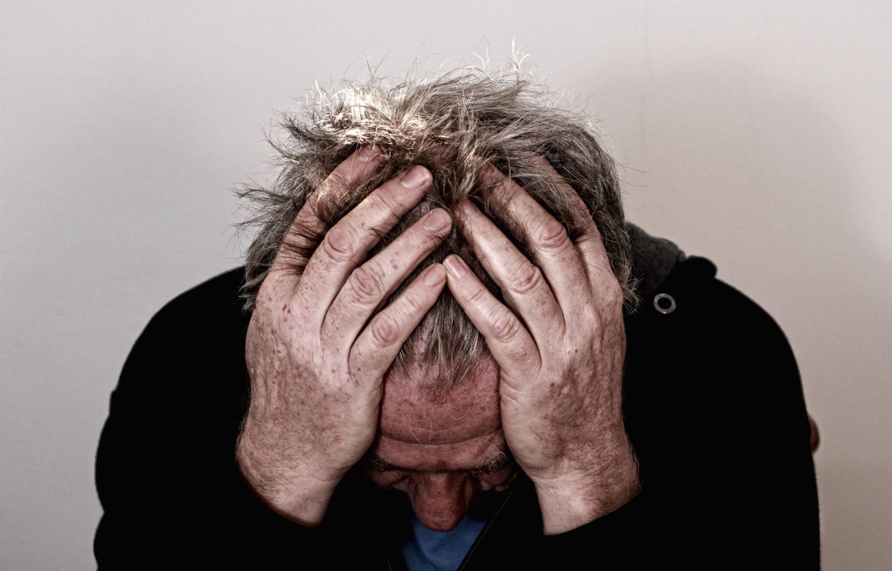 Trauriger Mann mit gesenktem Kopf.
